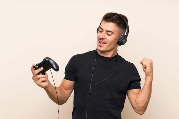 Het jonge knappe mens spelen met een videospelletjecontrolemechanisme over muur die een overwinning vieren