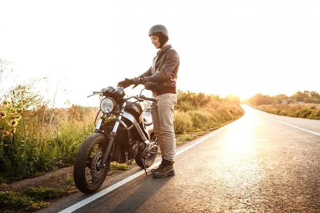 Het jonge knappe mens stellen dichtbij zijn motor bij plattelandsweg.