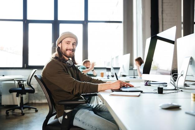 Het jonge knappe mensenwerk in bureau dat computer met behulp van