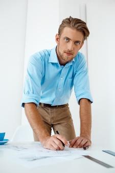 Het jonge knappe zekere peinzende zakenman werken die zich bij de schets van de lijsttekening bevinden. . witte moderne kantoor interieur