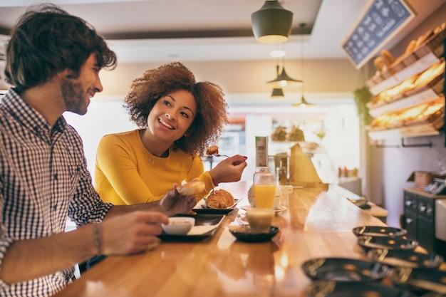 Het jonge koele paar die een ontbijt hebben, zij drinken thee en koffie in een bakkerij, sinaasappel