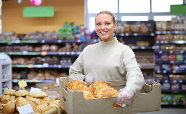 Het jonge krat van de vrouwenholding met bakkerijproducten in winkel. eigenaar van een klein bedrijf