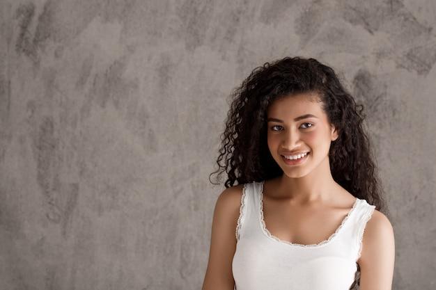 Het jonge krullende spaanse vrouw glimlachen