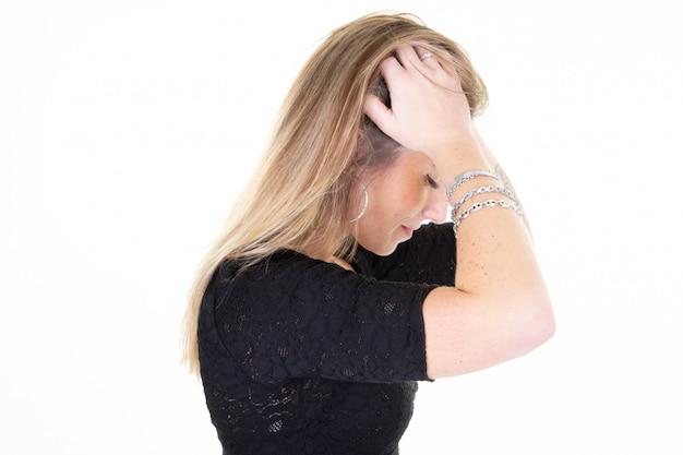 Het jonge lange haar van de blondevrouw over geïsoleerd wit dat aan hoofdpijn lijdt voor het hebben van bezinnings bedrijfswerk inspanning