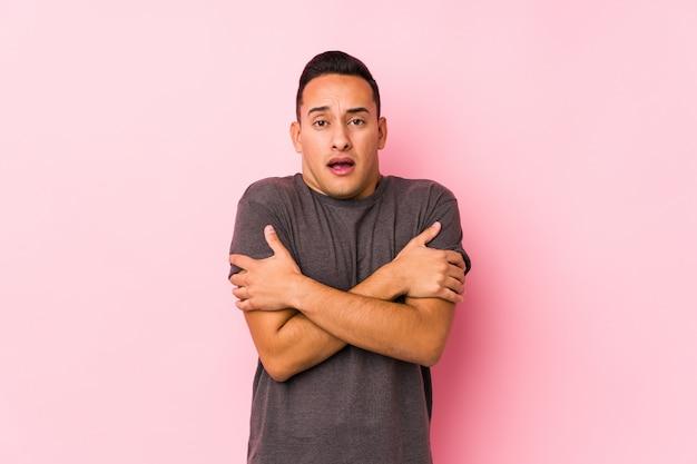 Het jonge latijnse mens stellen in een roze muurgaande koude toe te schrijven aan lage temperatuur of een ziekte.