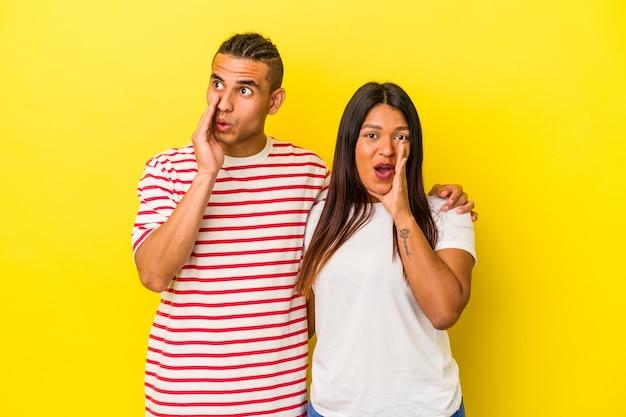 Het jonge latijnse paar dat op gele achtergrond wordt geïsoleerd zegt een geheim heet remnieuws en kijkt opzij