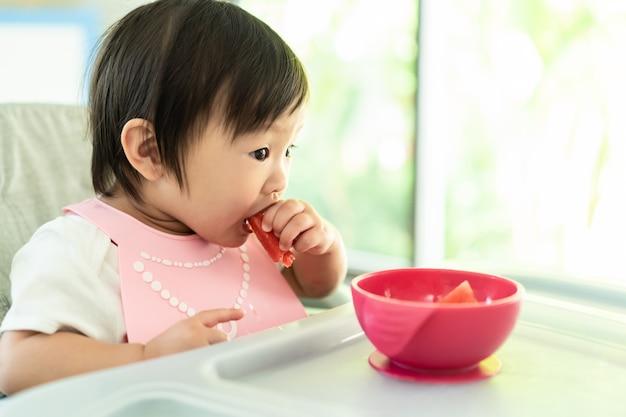 Het jonge leuke jonge geitje op baby hoge stoel het voeden de watermeloen van de zetelholding met glimlachgezicht thuis, geniet van zelf etend maaltijd met geluk.