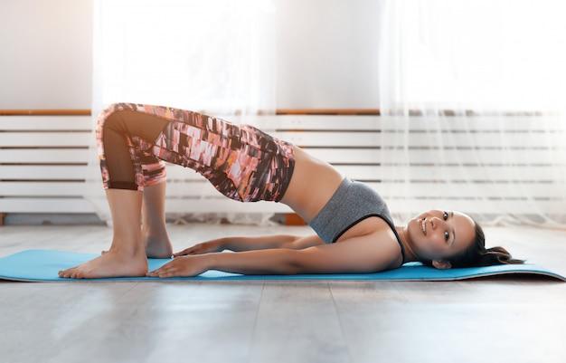 Het jonge leuke meisje beoefent yoga thuis, het nemen stelt