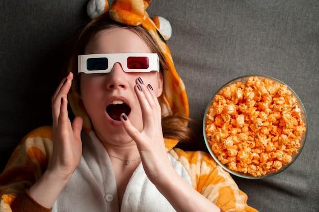 Het jonge leuke meisje ligt met 3d glazen eet popcorn en bekijkt een film