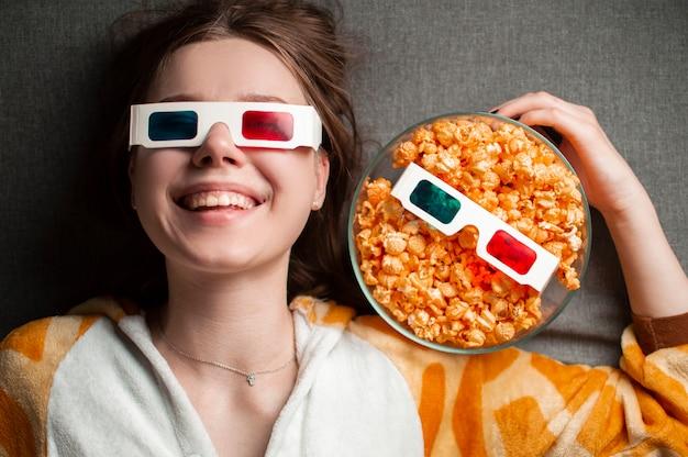 Het jonge leuke meisje ligt op een grijze achtergrond in 3d glazen met popcorn