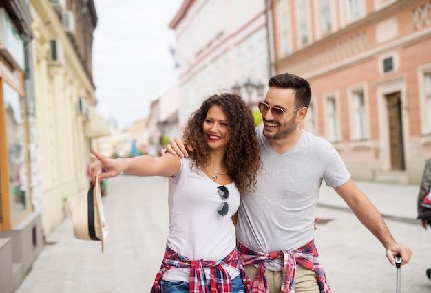 Het jonge leuke paar loopt onderaan de straat en doorbladert winkels en het richten.