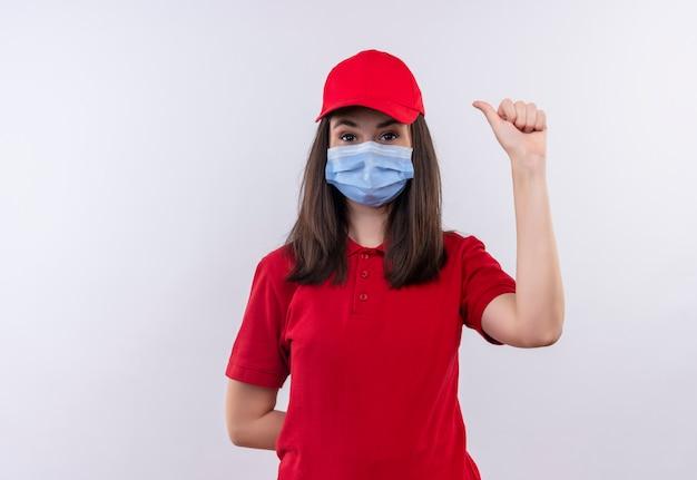 Het jonge leveringsmeisje dat rode t-shirt in rode glb draagt, draagt gezichtsmasker dat duimen op geïsoleerde witte achtergrond toont