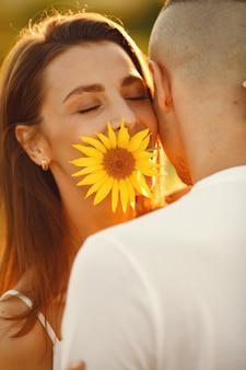 Het jonge liefdevolle paar kust in een zonnebloemgebied. portret van paar poseren in de zomer in veld.
