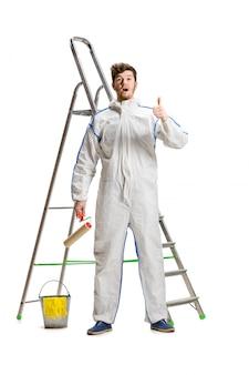 Het jonge mannelijke decorateur schilderen met een verfrol en een ladder die op witte muur wordt geïsoleerd.