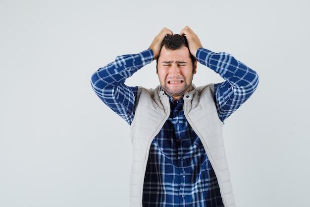 Het jonge mannelijke hoofd met handen in shirt, mouwloos jasje en op zoek stressvol. vooraanzicht.