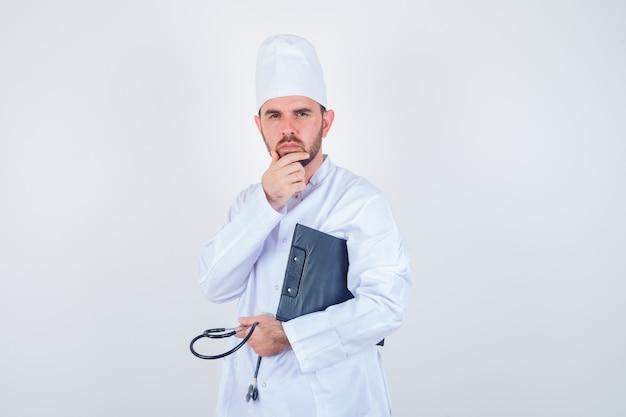 Het jonge mannelijke klembord, de stethoscoop van de artsenholding, die hand op kin in wit uniform houdt en nadenkend kijkt. vooraanzicht.