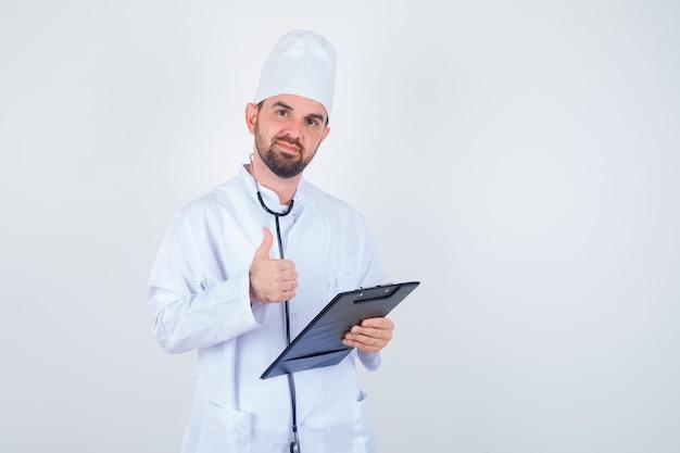 Het jonge mannelijke klembord van de artsenholding, die duim in wit uniform toont en er zelfverzekerd uitziet. vooraanzicht.