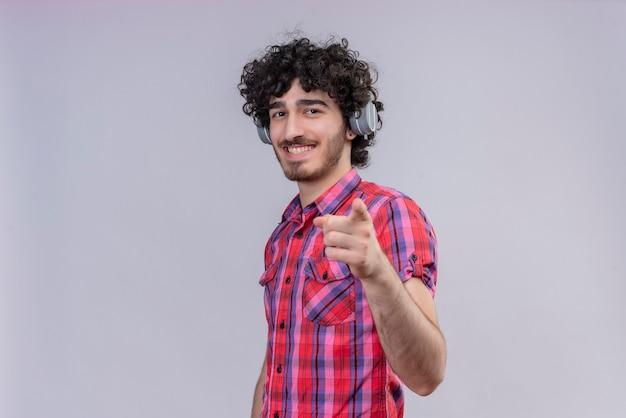 Het jonge mannelijke krullende haar isoleerde kleurrijke overhemdshoofdtelefoons wijzen