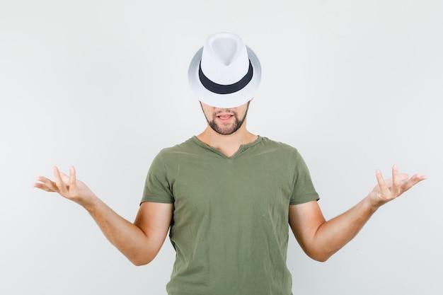 Het jonge mannetje dient groene t-shirt en hoed op en kijkt grappig