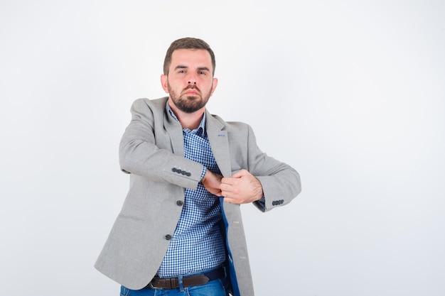 Het jonge mannetje dient zak van jasje in overhemd, spijkerbroek, kostuumjasje in en kijkt zelfverzekerd. vooraanzicht.
