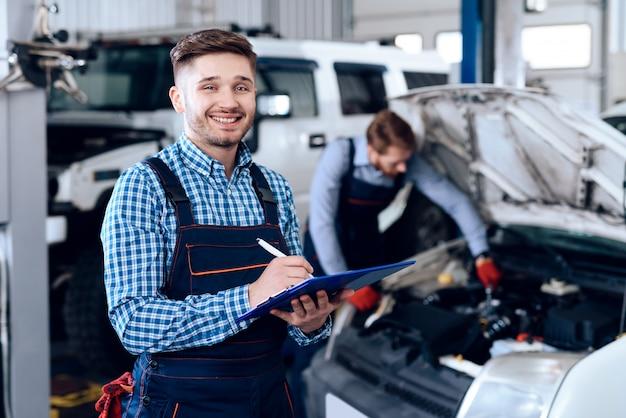 Het jonge mechanische posing in garage met tabletbureau.