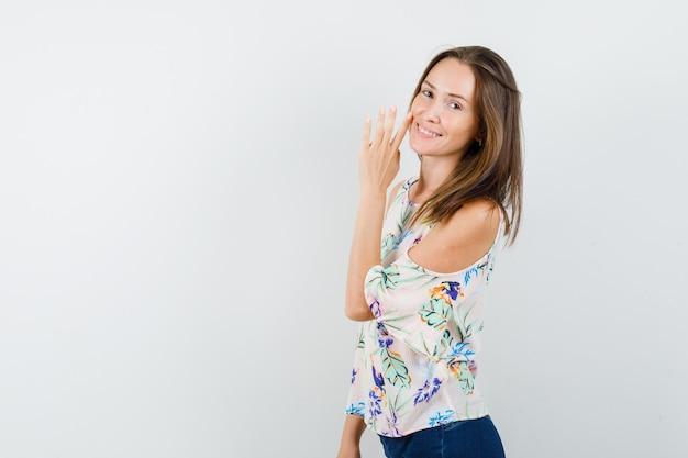 Het jonge meisje achter geheim vertellen dient overhemd, spijkerbroek in en kijkt vrolijk.