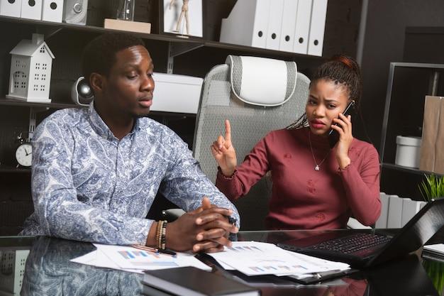 Het jonge meisje beantwoordt telefoon en toont het manenteken dat hij zittend aan tafel in kantoor heeft gewacht
