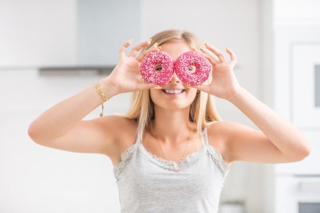 Het jonge meisje bedekte haar gezicht met roze donuts in de thuiskeuken. emotie ochtend bij het ontbijt.