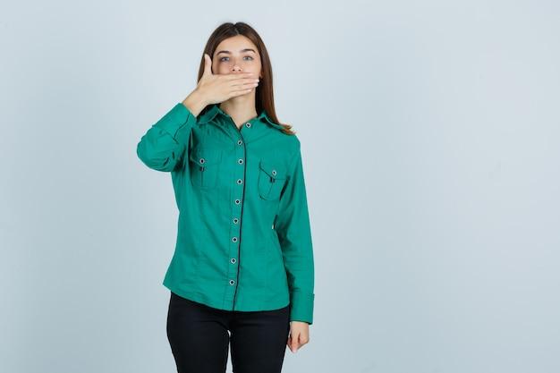 Het jonge meisje behandelt mond met dient groene blouse, zwarte broek in en kijkt beschaamd, vooraanzicht.