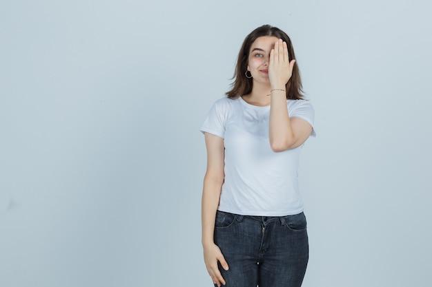Het jonge meisje behandelt oog met dient t-shirt, jeans in en kijkt gelukkig, vooraanzicht.