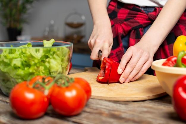 Het jonge meisje bereidt een vegetarische salade in de keuken voor, hakt zij peper, het proces om gezond voedsel, close-up voor te bereiden