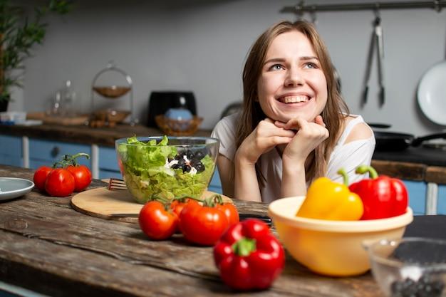 Het jonge meisje bereidt een vegetarische salade in de keuken voor, zij zit aan de tafel met voedsel en dromen, het proces om gezond voedsel te bereiden