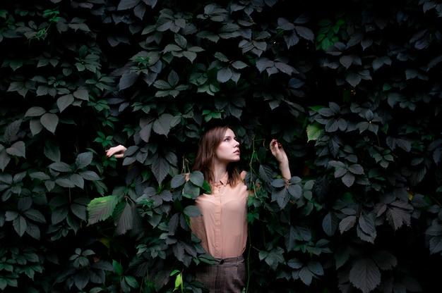 Het jonge meisje bevindt zich in groene bladeren alleen met aard, een vrouw raakt installaties en dromen, een concept een man in aard