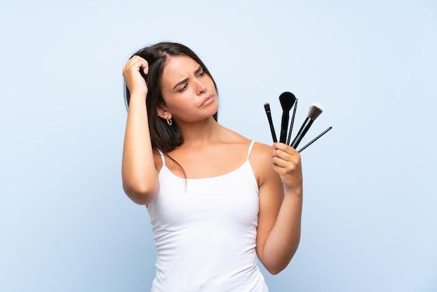 Het jonge meisje dat heel wat make-upborstel houdt die twijfels heeft en met verwart gezichtsuitdrukking