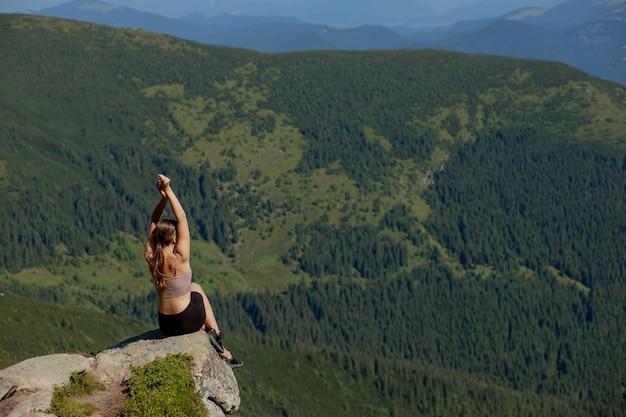 Het jonge meisje dat op de top van de berg zat, hief haar handen op in het bos