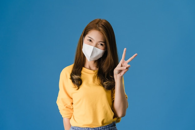Het jonge meisje dat van azië medisch gezichtsmasker draagt dat vredesteken toont, moedigt aan met gekleed in casual doek aan en bekijkt camera die op blauwe achtergrond wordt geïsoleerd. sociale afstand nemen, quarantaine voor coronavirus.