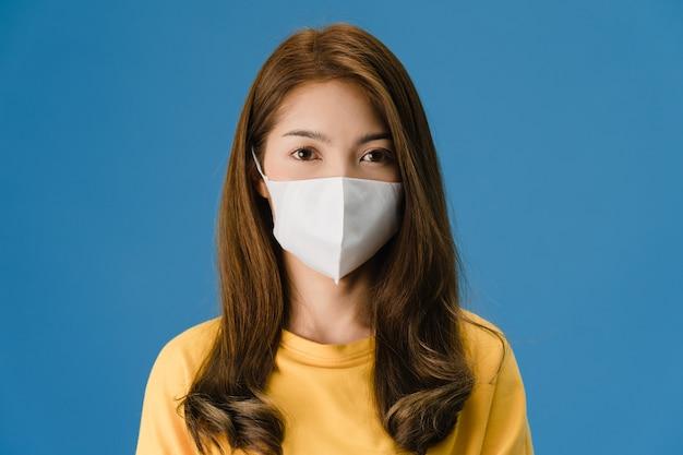 Het jonge meisje dat van azië medisch gezichtsmasker draagt met gekleed in vrijetijdskleding en camera bekijkt die op blauwe achtergrond wordt geïsoleerd. zelfisolatie, sociale afstand nemen, quarantaine voor coronaviruspreventie.
