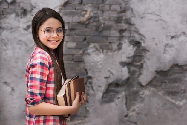 Het jonge meisje dat van de close-up een stapel van boeken houdt