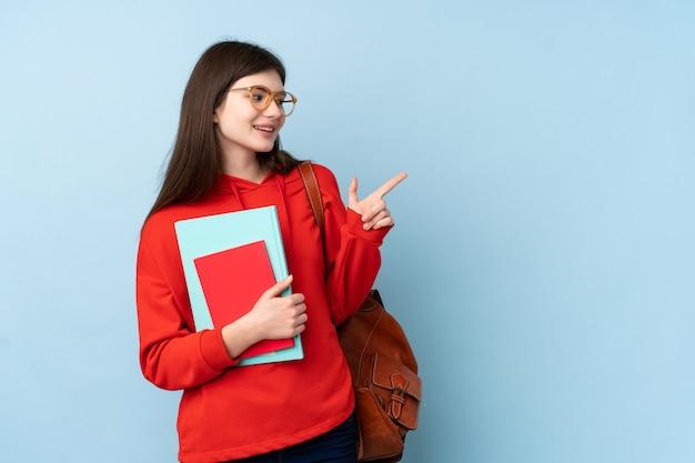 Het jonge meisje dat van de tienerstudent een salade over blauwe muur houdt die vinger richt aan de kant