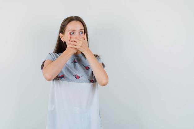 Het jonge meisje die mond strak behandelen met dient t-shirt in en kijkt bang, vooraanzicht.