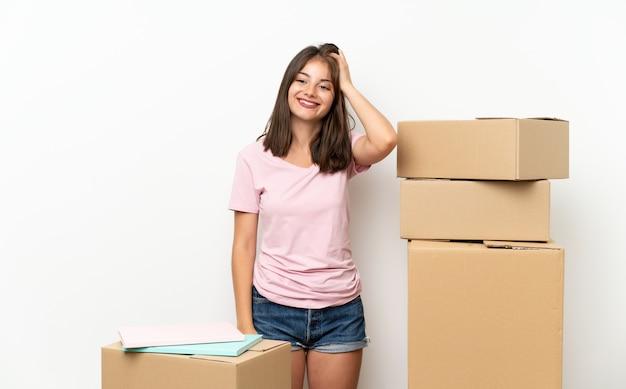 Het jonge meisje die zich in nieuw huis onder dozen bewegen die twijfels hebben met verwart gezichtsuitdrukking