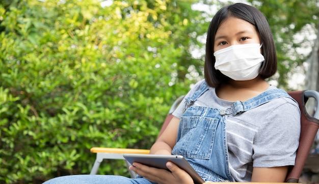 Het jonge meisje draagt een beschermingsmasker en gebruikt de tablet om online in de tuin thuis te studeren. voorkom contact met het coronavirus. concept van sociale afstand. onderwijs van thuis uit.