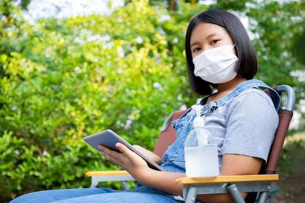 Het jonge meisje draagt een beschermingsmasker met alcoholgel en gebruikt de tablet om thuis online in de tuin te bestuderen. voorkom contact met het coronavirus.