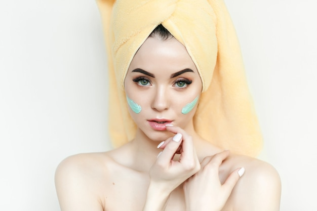 Het jonge meisje geniet room van gezichtsmasker met handdoek op hoofd.
