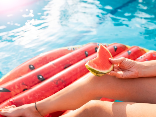 Het jonge meisje geniet van het zwembad en de mat met watermeloen, de zomerpret