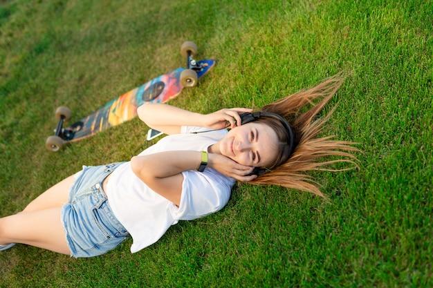 Het jonge meisje geniet van lag in groen gazon en het luisteren muziek na het berijden op haar logbord