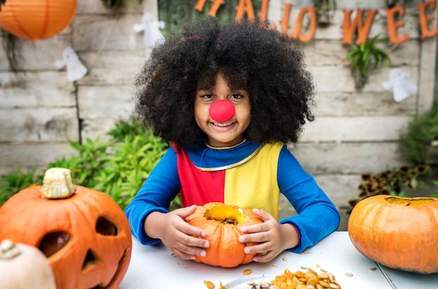 Het jonge meisje geniet van snijdend haar pompoen van halloween
