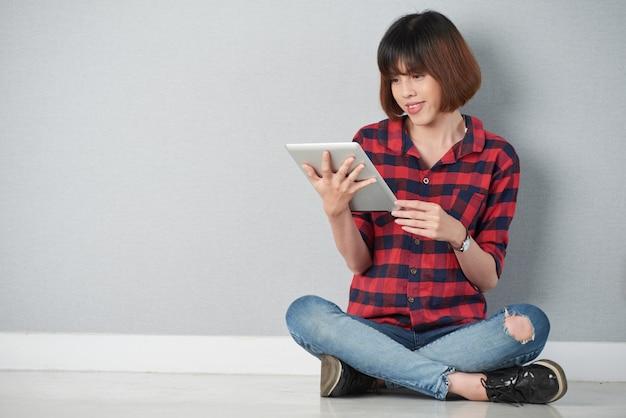 Het jonge meisje gezeten in lotusbloem stelt het doorbladeren van het net op haar digitale tablet-pc