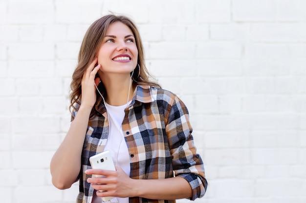 Het jonge meisje glimlacht en luistert naar muziek op de telefoon op een achtergrond van een witte bakstenen muur