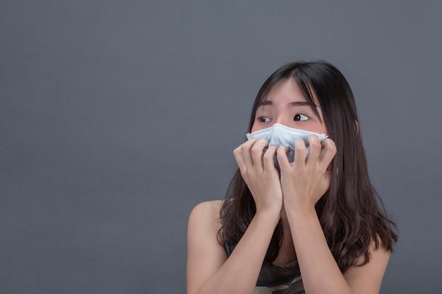 Het jonge meisje hoort masker terwijl met de hand het behandelen op grijze muur.
